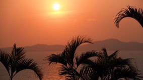 Beautiful sunset on the tropical beach. Orange sky and the sea with rocky island in the background. Beautiful sunset on a tropical beach. Orange sky and the sea stock footage