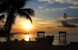 Beautiful sunset at tropical island. With silhouette of palm tree and peer on front Royalty Free Stock Photography
