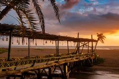 Beautiful sunset at tropical island restaurant resort. Vintage light bulbs Stock Photos