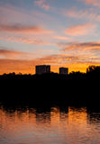 Beautiful Sunset with Two Buildings and Trees Reflected in Lake Royalty Free Stock Photo