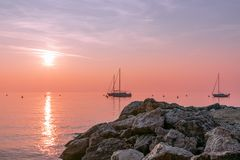 Beautiful sunset view during fog on Lake Garda with sailing boats and textured stones in the foreground. Lake garda, Italy royalty free stock photography