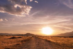 Beautiful sunset on the way to mountain lake. Surrounded by dry straw field Royalty Free Stock Photography