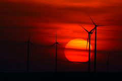 Beautiful sunset with wind turbines on the hill Stock Photos