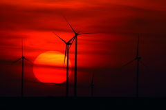 Beautiful sunset with wind turbines on the hill in summer Stock Photography