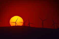 Beautiful sunset with wind turbines silhouettes on the hill Stock Photography