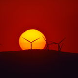 Beautiful sunset with wind turbines silhouettes on the hill Stock Photo