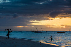 Beautiful sunset in Zanzibar Island. Locals enjoy the beach at sunset in Zanzibar Island. Image taken in a remote village of the island Royalty Free Stock Photos