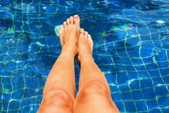 Beautiful Suntan Female Legs in Swimming Pool Stock Photo
