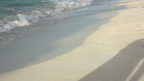 Beautiful suntanned female legs walking along seashore in waves, only legs in video and shadow moving on the sand stock video