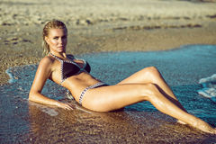 Beautiful suntanned glam blond woman with wet skin and hair lying on the beach and enjoying, her long legs washed by the sea Stock Images