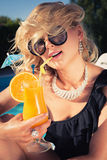 Beautiful, suntanned, young woman drinks cocktail Royalty Free Stock Photos