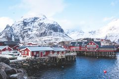Beautiful super wide-angle winter snowy view of fishing village A, Norway, Lofoten Islands, with skyline, mountains, famous fishin. G village with red fishing stock images