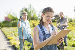 Beautiful supervisor writing on clipboard with gardeners standing in background at plant nursery Stock Photos