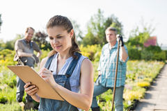 Beautiful supervisor writing on clipboard with gardeners standing in background at plant nursery Royalty Free Stock Photography