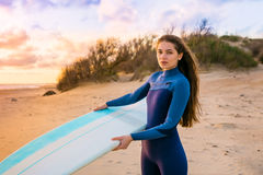 Beautiful surf girl with long hair holding surfboard on a beach at sunset or sunrise. Surfer and ocean Stock Photos
