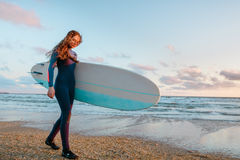 Beautiful surf girl with long hair holding surfboard go on beach at sunset or sunrise. Royalty Free Stock Image