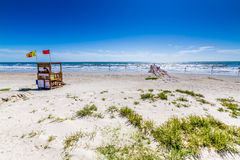 Beautiful Surf and Sand on a Summertime Ocean Beach. White sands and life guard station.  Blue skies Stock Image