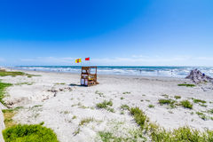 Beautiful Surf and Sand on a Summertime Ocean Beach. With wooden life guard station Stock Photography