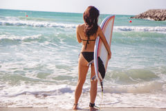 Beautiful surfer brunette girl on the beach at sunset time Stock Photography