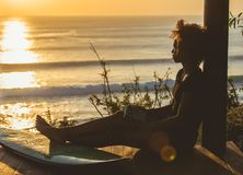 Beautiful surfer girl with afro hair style reading book on top of the cliff at sunset. On the beach in front of seascape in Bali, Indonesia. copy space stock photos