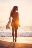 Beautiful surfer girl on the beach at sunset. Beautiful sexy young surfer girl in bikini with surfboard on the beach at sunset Royalty Free Stock Images