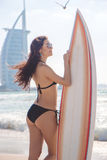 Beautiful surfer girl on the beach at sunset time. Beautiful slim surfer girl on the beach at sunset Stock Photo