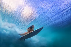 Beautiful surfer girl diving under water with surf board. Sportive girl in bikini in action. Surfer with surf board dive underwater under breaking ocean wave stock photography