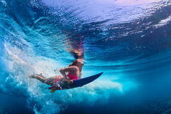 Beautiful surfer girl diving under water with surf board. Young active girl wearing bikini in action - surfer with surf board dive underwater under big ocean royalty free stock photos