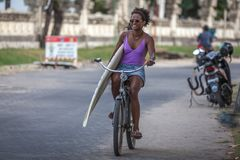 Beautiful surfer girl in purple bikini with afro hairstyle riding bicycle with one hand. Carrying surfboard under her arm at Kuta beach, Bali, Indonesia royalty free stock photography