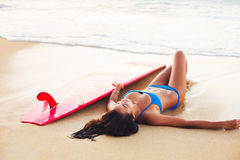 Beautiful Surfer Girl Relaxing on the Beach Royalty Free Stock Photography