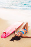 Beautiful Surfer Girl Relaxing on the Beach Royalty Free Stock Images