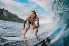 Beautiful surfer girl on surfboard. Woman in ocean during surfing. Surfer and barrel wave stock image