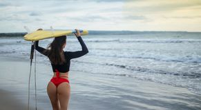 Beautiful surfer girl walking down to the beach for sunset surf session carrying blue - yellow surfboard on head with back in royalty free stock image