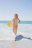 Beautiful surfer girl walking from the sea with her surfboard Stock Images