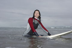 Beautiful Surfer Sitting On Surfboard In Water At Beach Royalty Free Stock Photography