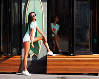 A beautiful surfer tanned long-legged girl in white shorts, a turquoise shirt, white sneakers and sunglasses posing at a surf in a Royalty Free Stock Photo