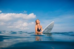 Beautiful surfer woman in swimwear with surfboard. Surfer with surfboard in tropical ocean. Royalty Free Stock Photos