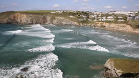 Beautiful surfing beach near Newquay of Mawgan Porth north Cornwall England uk on a summer day with blue sky on the Cornish Atlant. Surfing waves in Mawgan Porth stock footage