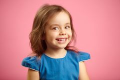 Beautiful surprised child girl with cute smile and sincere look, is in a good mood, expresses joy and happiness, close. Up kid portrait on pink isolated royalty free stock photos