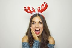 Beautiful surprised christmas girl with reindeer horns on her head with gray background. Beautiful surprised christmas girl with reindeer horns on her head on Royalty Free Stock Photo