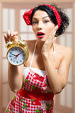 Beautiful surprised pinup girl holding alarm clock. Close up picture of beautiful surprised pinup girl wearing red apron being late in the morning and holding a stock photo
