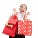 Beautiful Surprised Shopping Young Woman. Beautiful Surprised Happy Young Woman Holding Shopping Bags and Looking Away. Red and White Colors Stock Photos
