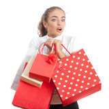 Beautiful Surprised Shopping Young Woman. Beautiful Surprised Young Woman Holding Shopping Bags and Looking Away. Red and White Colors Royalty Free Stock Photo