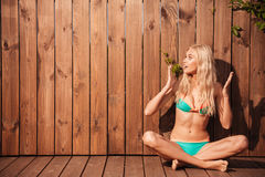 Beautiful surprised woman in bikini looking away over wooden background Royalty Free Stock Images