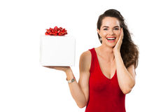 Beautiful surprised woman holding gift. A beautiful happy surprised woman in a red dress smiling and holding a big white gift box. Isolated on white stock images