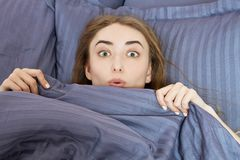 Beautiful surprised woman lying down in the bed after sleeping. Teen girl with open eyes with grey blanket. Morning concept. View. From above with place for royalty free stock photography