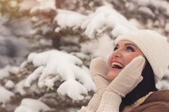 Beautiful woman in winter park. Young beautiful woman in winter park, touching her face skin,  laughing and looking up. Selective focus, copy space, vintage Stock Images