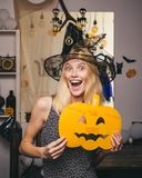 Beautiful surprised woman in witches hat and costume. Woman posing with Pumpkin. Halloween Witch. Beautiful young. Surprised woman in witches hat and costume stock images