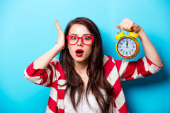 Beautiful surprised young woman with alarm clock standing in fro. Nt of wonderful blue background royalty free stock images