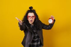 Beautiful surprised young woman with alarm clock standing in fro. Nt of a yellow background royalty free stock photography